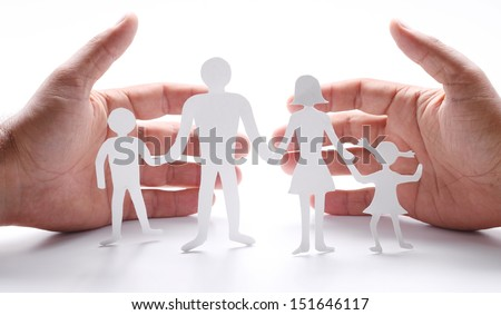 Cardboard figures of the family on a white background. The symbol of unity and happiness. Hands gently hug the family. - stock photo