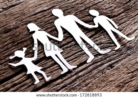 Cardboard figures of the family on a wooden table. The symbol of unity and happiness. - stock photo