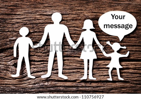 Cardboard figures of the family on a wooden table. The symbol of unity and happiness. Above the daughter bubble, which you can enter your message. - stock photo