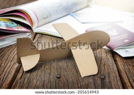 cardboard plane on wooden table - stock photo