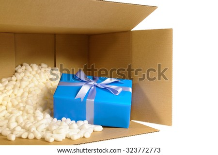 Cardboard shipping delivery box with one unique blue Christmas gift inside and polystyrene packing pieces. - stock photo