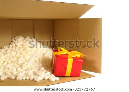 Cardboard shipping delivery box with one unique red Christmas gift inside and polystyrene packing pieces. - stock photo