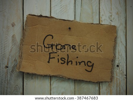 Cardboard sign on a wooden background saying gone fishing. Vintage filter applied. - stock photo