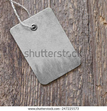 Cardboard tag on wooden background - stock photo