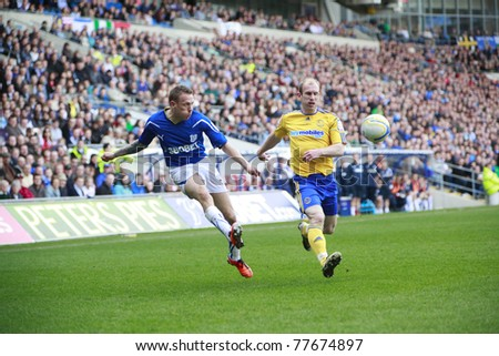 CARDIFF - APRIL 02: Craig Bellamy (left) of Cardiff City FC attempting a cross past Gareth Roberts (right) of Derby County FC during their Championship match, April 02, 2011 in Cardiff, Wales. - stock photo