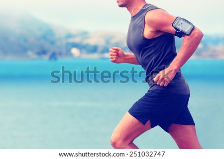 Cardio runner running listening smartphone music. Unrecognizable body jogging on ocean beach or waterfront working out with heart rate monitor app device and earphones in summer. - stock photo