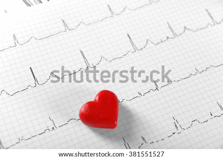 Cardiogram chart with small red heart on table closeup - stock photo