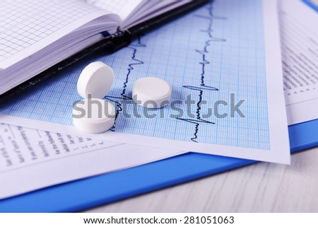 Cardiogram with pills on table, closeup - stock photo