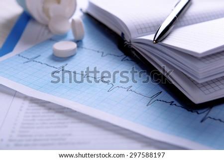 Cardiogram with pills on table, closeup - stock photo