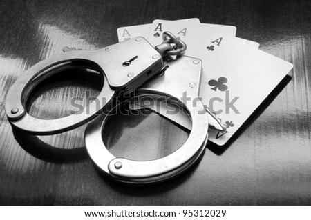 Cards and handcuffs on wooden table - stock photo
