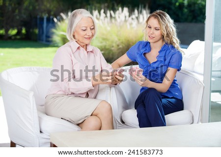Care aid playing card game with senior woman in retirement home. - stock photo