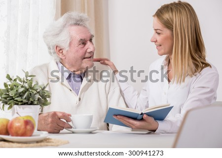 Care assistant and elder man reading book - stock photo
