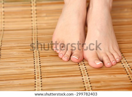 Care for beautiful woman legs on the bamboo floor - stock photo