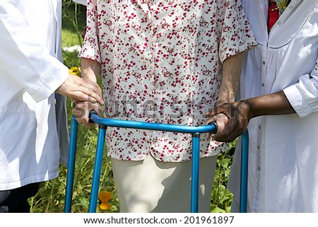 care giver helping senior patient with walker  outdoor - stock photo