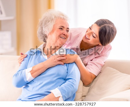 Care of senior woman at home sitting on the couch - stock photo