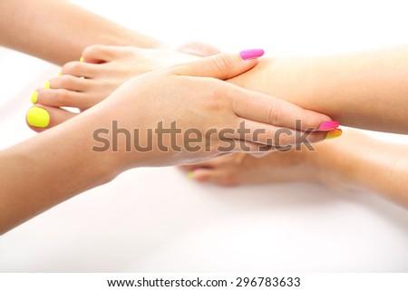 Care treatment, relaxing foot massage. Beautician massaging woman's foot, acupressure treatment - stock photo