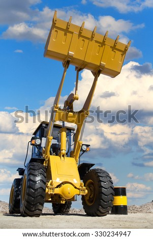 Career in the tractor, the tractor on the background of the cloudy sky, a large tractor with a bucket on the sand, transport of building materials, a barrel of fuel and tractors, mining in the quarry. - stock photo