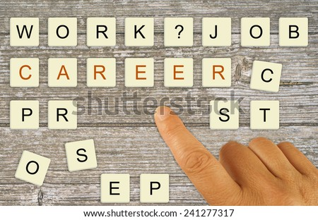 Career planning, recruitment etc. Finger pointing making choice with letter tiles. - stock photo