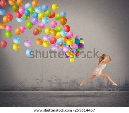 Carefree and happy girl jumping with balloons - stock photo
