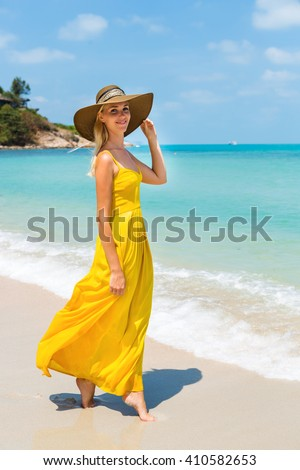 Carefree beautiful fashion blonde woman in beach straw hat walking barefoot by sand of tropical beach and holding her long yellow dress. Natural woman beauty. Lady touch her hat and smiles. - stock photo