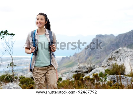 Carefree brunette girl walks outdoors hiking and exploring. she is cheerful and happy - stock photo