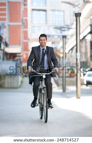 Carefree businessman riding a bicycle outdoors go to work  - stock photo