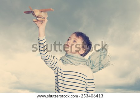 Carefree child with a airplane toy outdoors - stock photo