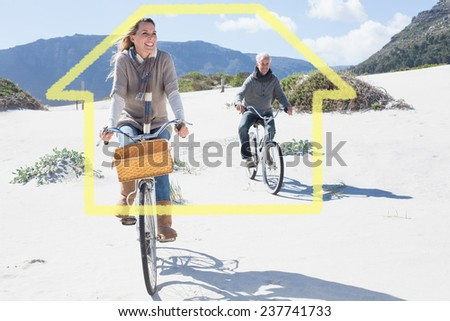 Carefree couple going on a bike ride on the beach against house outline - stock photo