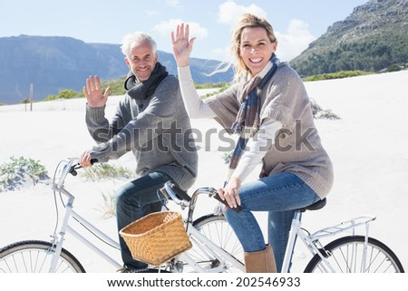 Carefree couple going on a bike ride on the beach waving at camera on a bright but cool day - stock photo
