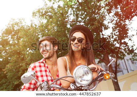 carefree couple having fun riding a scooter together. Young friends couple posing on a retro scooter outdoors with copy space - stock photo