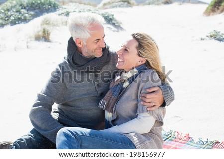 Carefree couple having picnic on the beach on a bright but cool day - stock photo