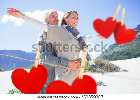 Carefree couple hugging on the beach in warm clothing against hearts hanging on a line - stock photo