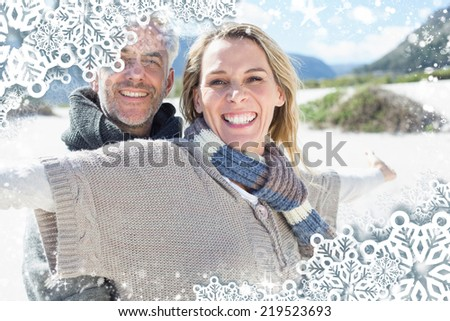 Carefree couple standing on the beach in warm clothing against snow - stock photo