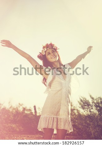 Carefree elated cheering woman in spring or summer desert landscape full of hope and vitality.  Multiracial girl raising her arms up smiling happy. Mixed race Latina Caucasian female model. - stock photo