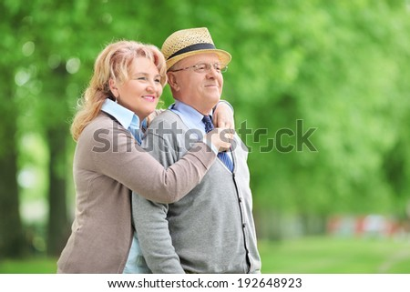 Carefree elderly couple hugging outdoors - stock photo