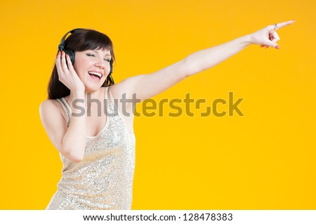 Carefree girl listening to music in headphones and gesturing, yellow background - stock photo