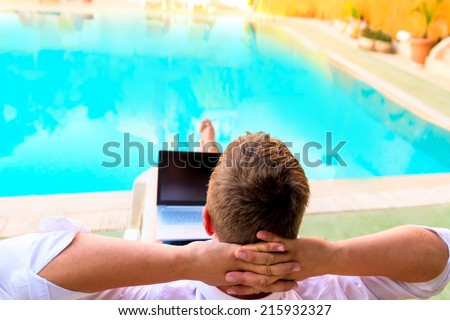 carefree male relaxes on a sun lounger  - stock photo