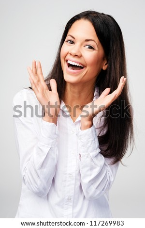 carefree portrait of a woman laughing and having fun. real person on grey background - stock photo
