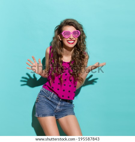 Carefree smiling girl. Beautiful woman in heart shaped glasses is smiling with arms outstretched. Three quarter length studio shot on teal background.  - stock photo