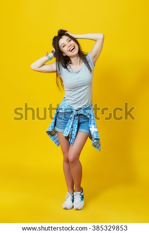 Carefree summer. Laughing beautiful girl posing over yellow background. Full length studio shot of happy teenage woman - stock photo