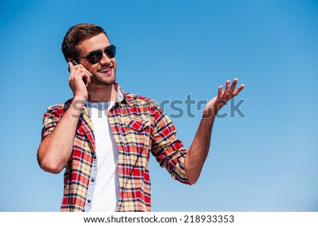 Carefree talk. Cheerful young man in sunglasses talking on mobile phone and gesturing while standing outdoors with blue sky as background  - stock photo