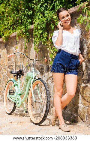 Carefree talk with friend. Beautiful young woman talking on the mobile phone and smiling while standing near her vintage bicycle  - stock photo