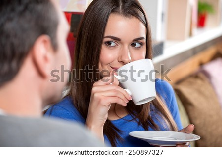 Carefree time in cafe. Beautiful young couple looking at each other and smiling while enjoying coffee in cafe together with selective focus - stock photo