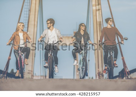 Carefree time with friends. Four young people riding bicycles along the bridge and smiling - stock photo