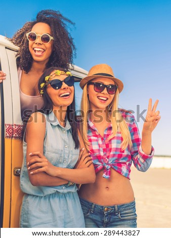 Carefree time with friends. Happy young African woman looking out from the retro minivan while two her friends standing near her - stock photo