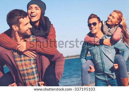 Carefree time with friends. Two beautiful young couples walking by the beach and smiling - stock photo