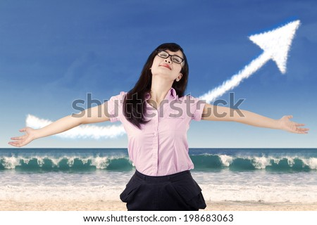 Carefree woman celebrating her success with upward arrow sign - stock photo