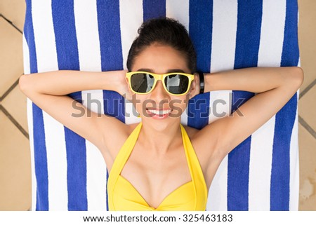 Carefree woman enjoying sunny day at the pool, view from above - stock photo