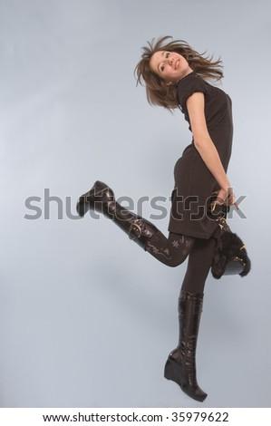 Carefree woman in black kicking leg up behind her. - stock photo