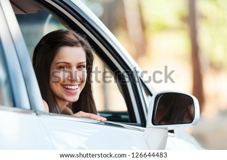 carefree woman in car driving with smile and confidence - stock photo